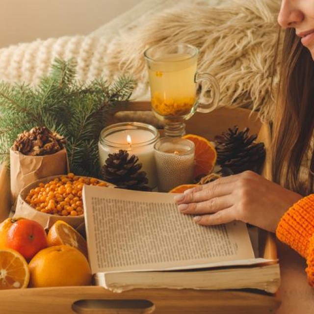 Soft cozy photo of woman in warm orange sweater on the bed with cup of tea and fruit. Girl sitting on the bed with old books. Reading a book, concepts of home and comfort, place for text