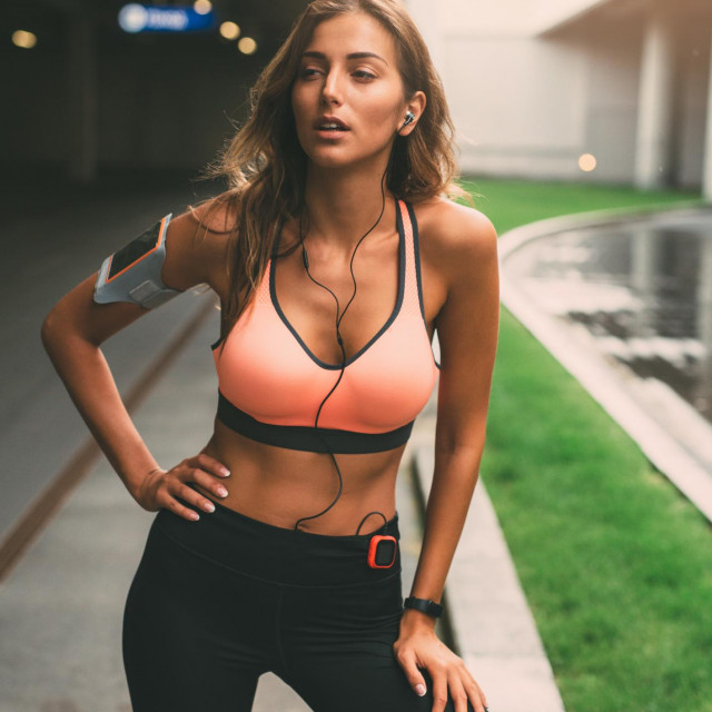 Beautiful young woman resting outdoor after exercise.