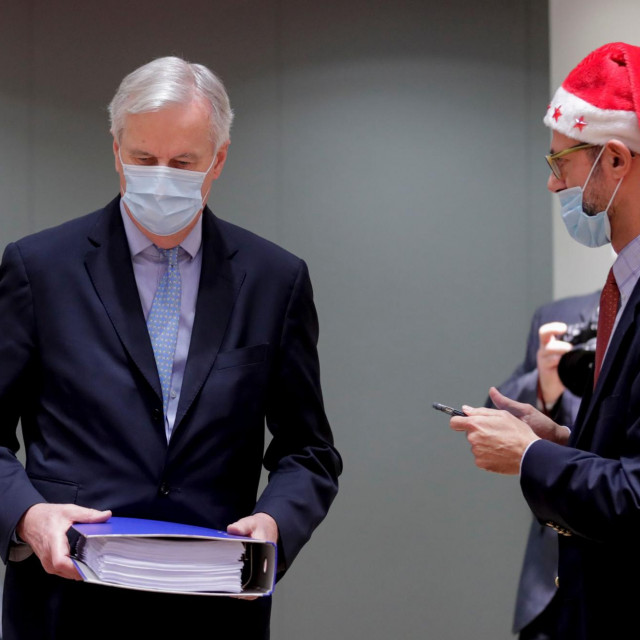 EU Chief Negotiator for Brexit Michel Barnier (L) is watched by a Greek representative, while carrying a folder containing the 2000 page 'Brexit Trade Deal' as he arrives ahead of a special meeting of The Committee of the Permanent Representatives of the Governments of the Member States to the European Union (Coreper) at the European Council in Brussels on December 25, 2020. (Photo by Olivier HOSLET/POOL/AFP)
