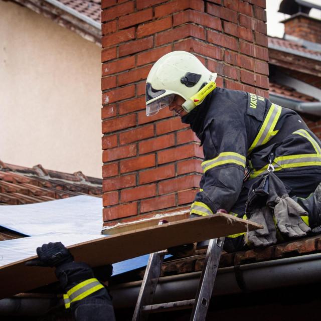 Vatrogasac radi na saniranju oštećenog krova