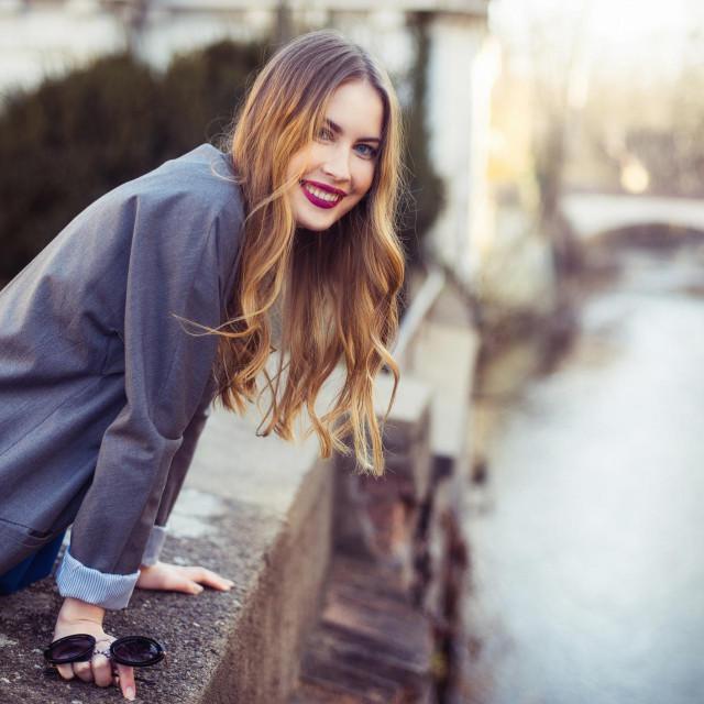 Beautiful smiling woman walking in the city near river embankment