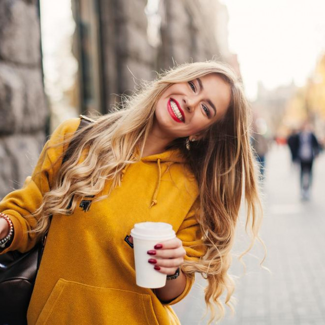 Stylish happy young woman wearing boyfriend jeans, white sneakers bright yellow sweatshirt.She holds coffee to go. portrait of smiling girl in sunglasses and bag