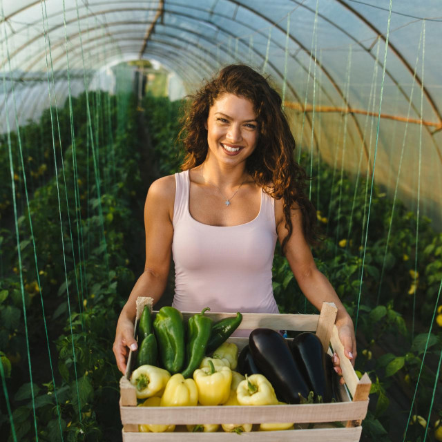Young woman holding crate full of vegetables in a greenhouse