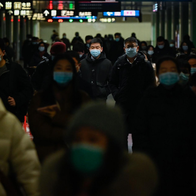Passengers walk in a subway station in Beijing on January 18, 2021. (Photo by WANG Zhao/AFP)