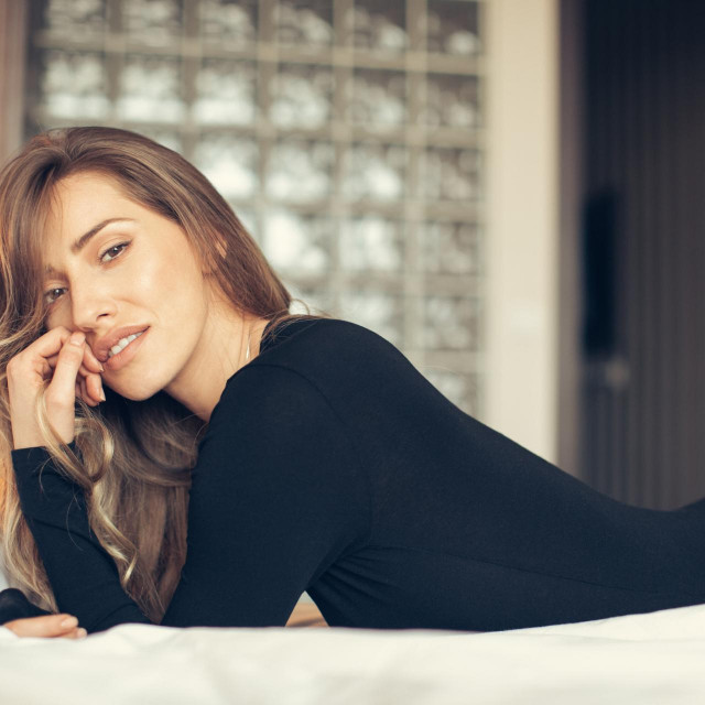 Portrait of young sensual woman lying on bed and looking at camera. She is beautiful