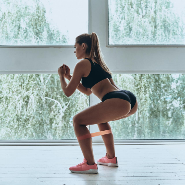 Modern young woman in sport clothing crouching using resistance band while exercising in the gym