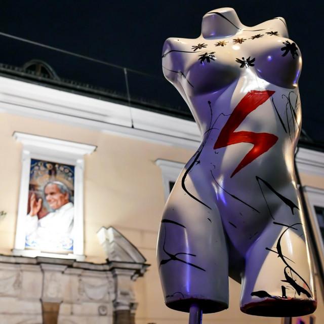 Crvena munja simbol je prosvjeda protiv zakona; u pozadini fotografija nadbiskupa MarekaJedraszewska