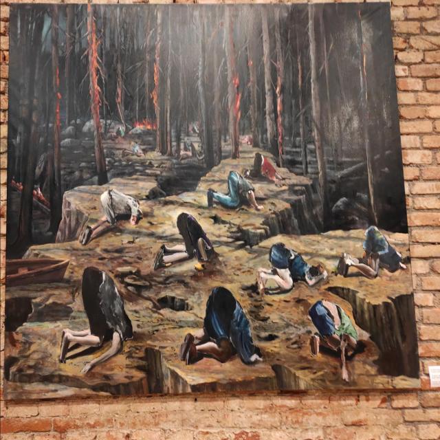 Jedan od boljih radova na izložbi pokazuje ljude koji su zabili glavu u zemlju