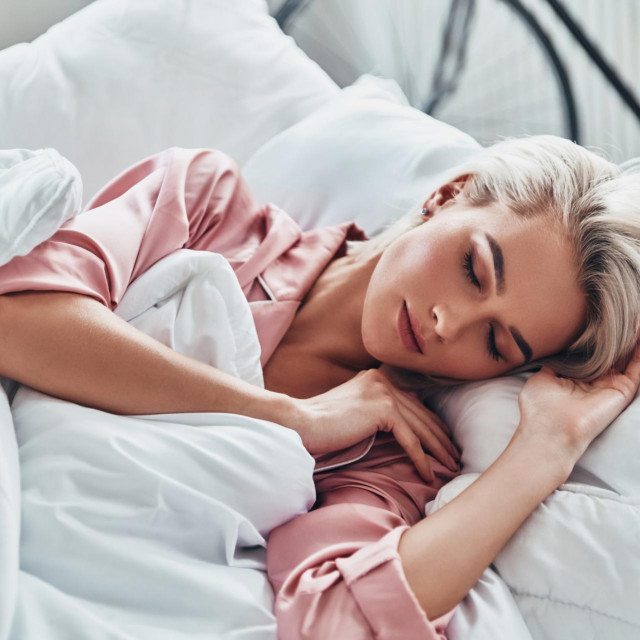 Top view of attractive young woman sleeping while lying in bed at home