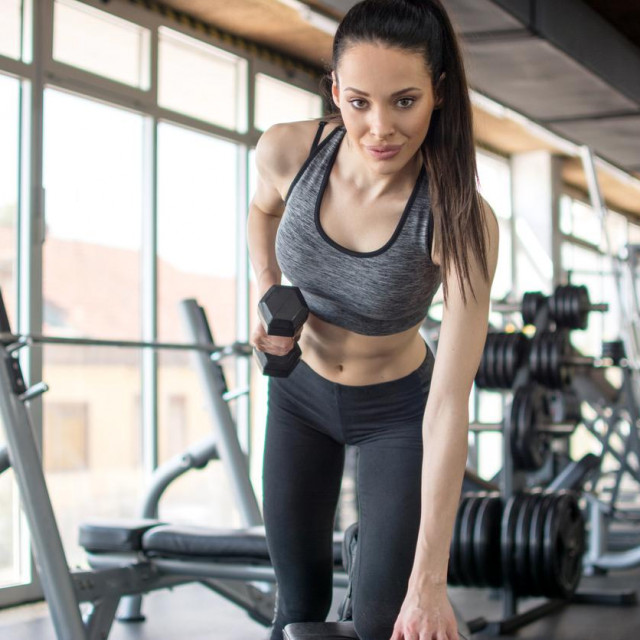 Young sporty woman flexing muscles with dumbbell on weight bench at gym.