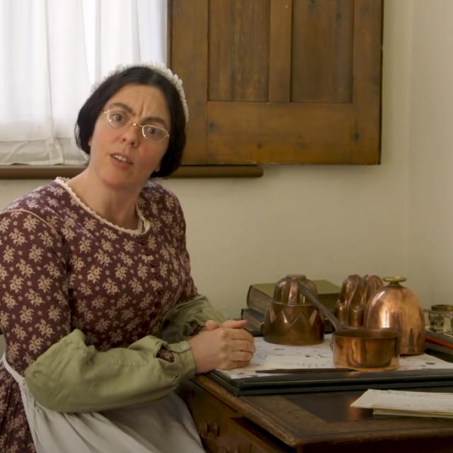 Glumica odjevena u starinsku odjeću pokazuje kako se nekad čistilo bakreno posuđe
