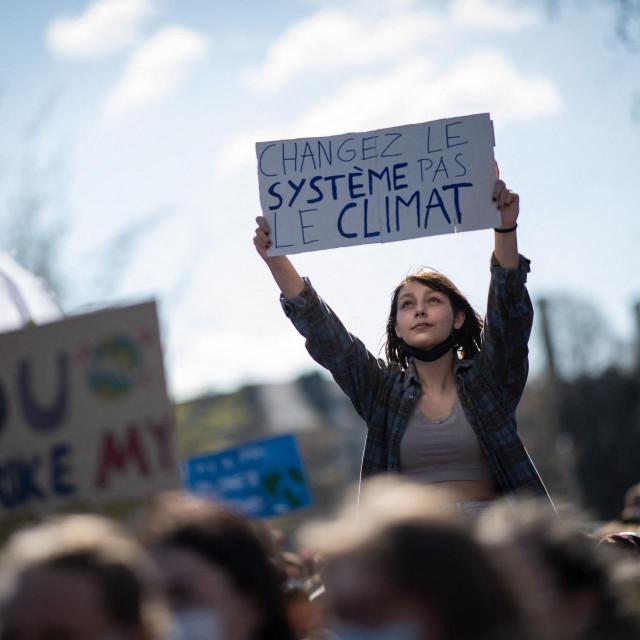 """Prosvjednica u Francuskoj drži natpis """"Promijenite sustav, a ne klimu"""", ilustracija"""