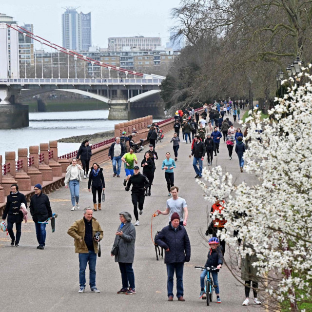 People take their daily exercise beside the River Thames in Battersea Park in London on March 28, 2021. - From Monday, England's stay-at-home order to combat the spread of the coronavirus will be relaxed to enable groups of up to six people to meet outside. The government plans to allow outdoors drinking in pub gardens, and non-essential retail such as hairdressers, from April 12. (Photo by Justin TALLIS/AFP)
