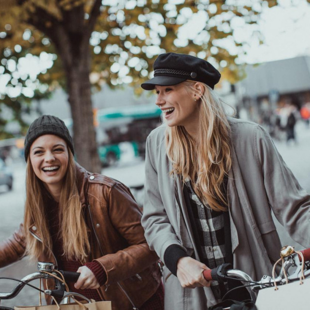 Photo of a young women leading their bikes through city