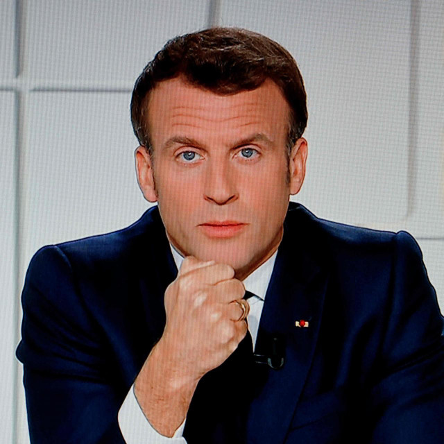French President Emmanuel Macron is seen on a TV screen as he speaks during a televised address on the new Covid-19 restrictions from the Elysee Palace in Paris on March 31, 2021. (Photo by Ludovic MARIN/AFP)