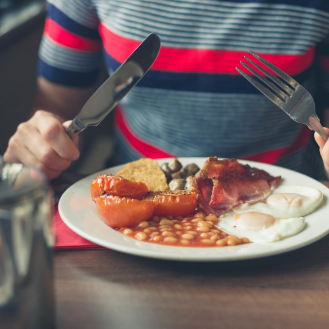 A young woman is having a traditional english breakfast in a diner