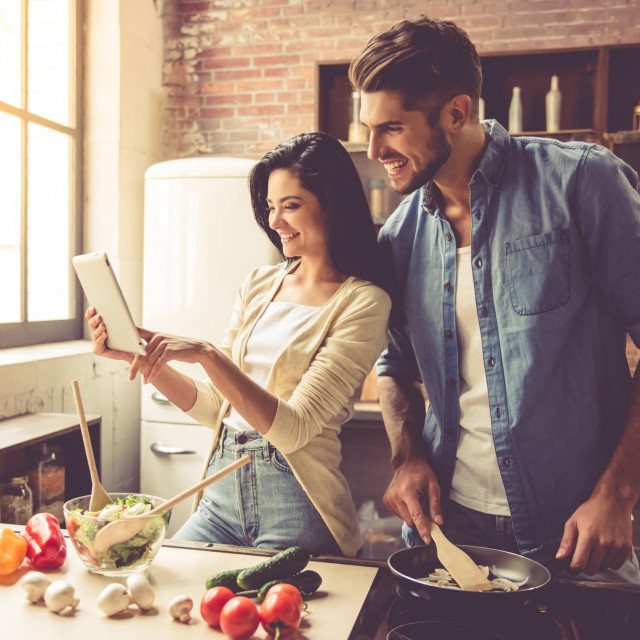 Beautiful young couple is using a digital tablet and smiling while cooking in kitchen at home