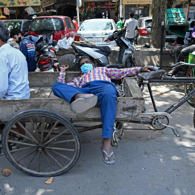 Rickshaw drivers rest along a street in the old quarters of New Delhi on April 19, 2021, as India's capital will impose a week-long lockdown from tonight, officials said, while the megacity struggles to contain a huge surge in Covid-19 cases with hospitals running out of beds and oxygen supplies low. (Photo by Sajjad HUSSAIN/AFP)