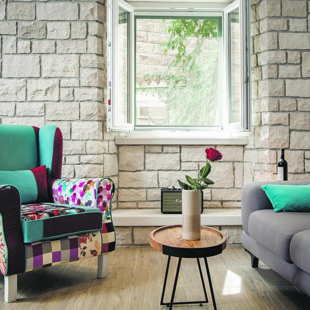 Dnevni boravak sastoji se od dvosjeda iz Art Interijera u sivoj tkanini s plavim šavovima, višebojne fotelje iz Emmezete i dva stolića u kombinaciji željeza i drva iz Lesnine