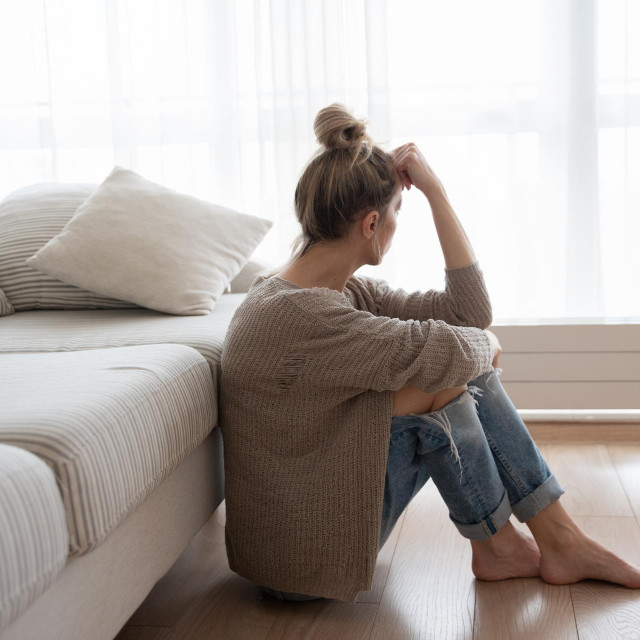 A depressed woman is sitting on the floor in the living room.