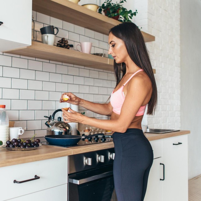 Fit woman in kitchen cracking egg into frying pan Preparing breakfast