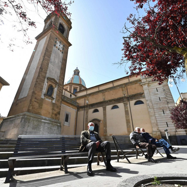 People sit near the Basilica Cathedral of San Giuliano at Piazza Umberto I in Caltagirone, Sicily, on April 27, 2021. - Italy has long suffered one of the lowest birth rates in Europe, but the situation has been exacerbated by the coronavirus pandemic -- saddling the country with problems that go well beyond empty cribs. (Photo by Andreas SOLARO/AFP)