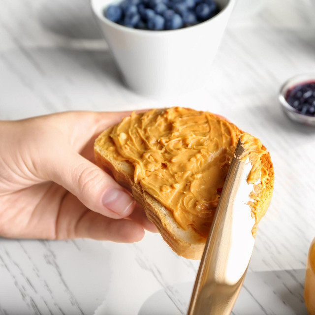 Woman spreading peanut butter on slice of bread near kitchen table