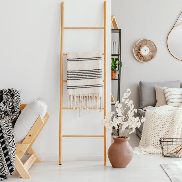 Wooden ladder with blanket between elegant settee with patterned blanket and comfortable bed with light grey bedding, real photo