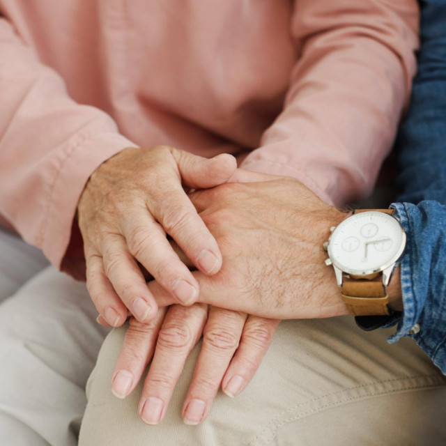 Close up of Caucasian male and female hands holding and caressing. Motherhood love. Senior mother and adult son supporting each other and hugging. Old woman and young man.