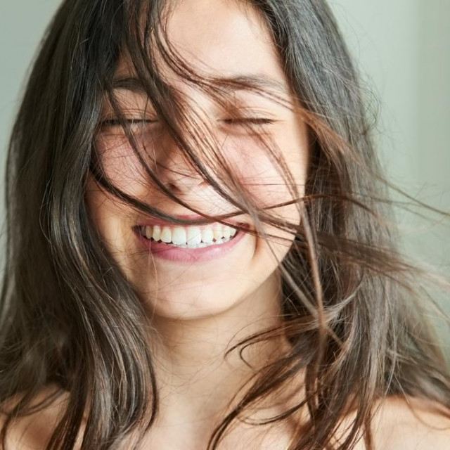 Close-up portrait of a beautiful girl smiling with her hair blowing in wind