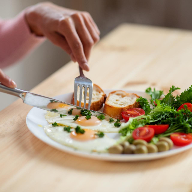 Woman eating tasty breakfast in kitchen, having plate with eggs, bread, olives and salad. Unrecognizable female using fork and knife while enjoying her delicious meal, cropped image, closeup