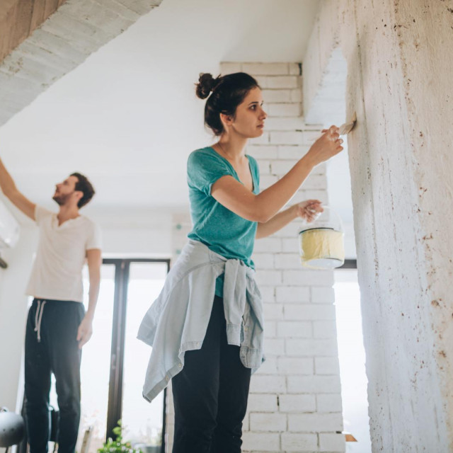Young couple painting their living room