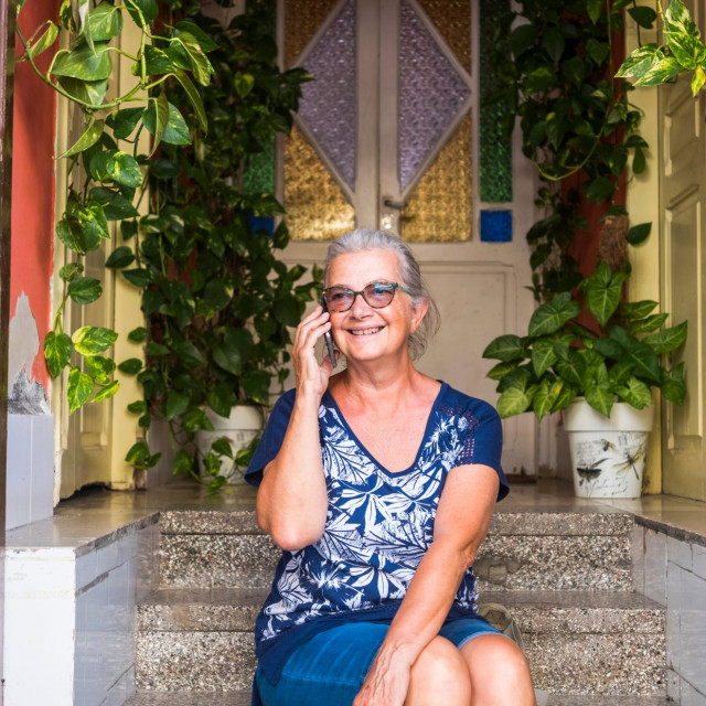 Portrait of a senior woman white hair talking with smart phone while sitting and relaxing on staircase, smiling - active retired people enjoying freedom and vacation