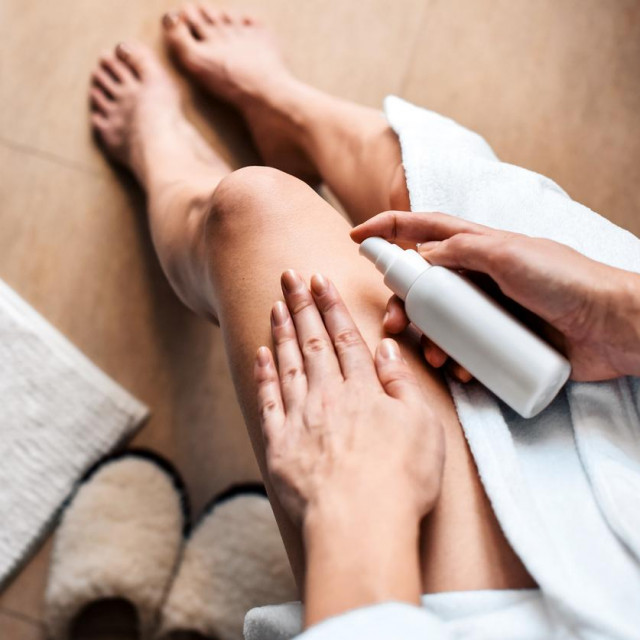 The girl in the bathroom puts anti-cellulite cream, serum on the legs and body. Body care concept.