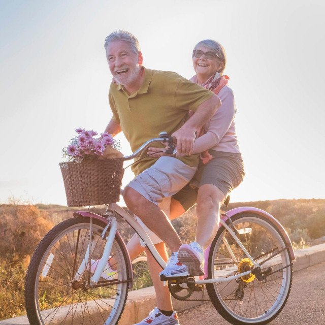 joy and happiness for adult married couple start and have fun traveling on the same bike in outdoor activity with sun backlight on the background. clear and bright image for smile and laugh people.