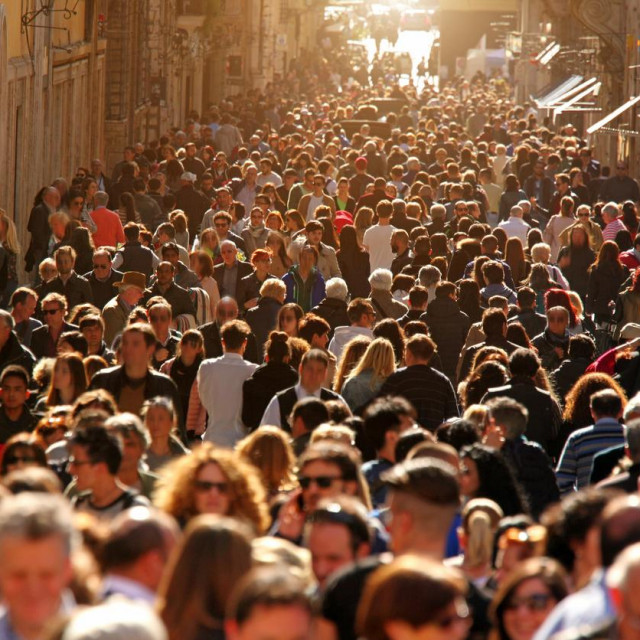 Large group of people crowding Rome's downtown streets in a sunny day. On a warm day the historic downtown of Rome, Italy, is flooded by people and tourists enjoying monuments and famous places. Horizontal composition.