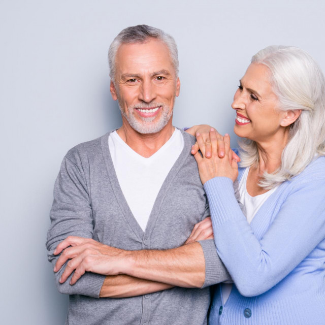 Happy excited lovely tender gentle cute elderly people are smiling and embracing, isolated on grey background