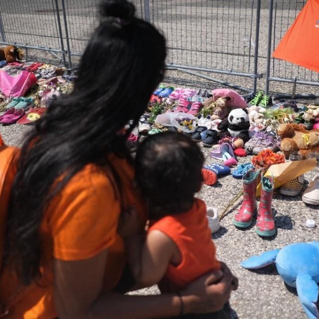 Pred jednom od škola u kojoj su otkriveni posmrtni ostaci djece ljudi ostavljaju dječje cipelice, plišane igračke i cvijeće