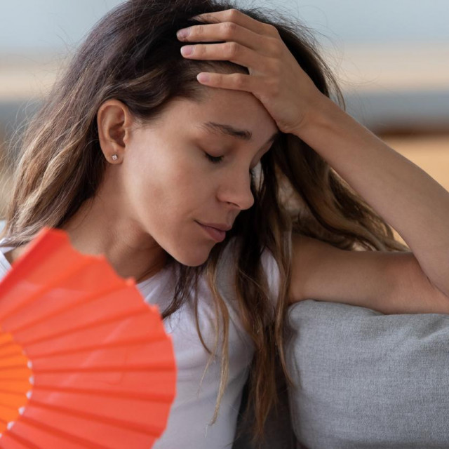 Close up view millennial woman sitting on couch exhausted by hot weather closed eyes feels unwell dying of heat holding in hand orange fan using it for reducing too hot temperature indoors concept