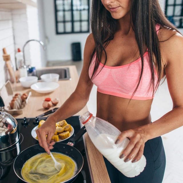 Sporty woman holding frying pan and mixing omlete