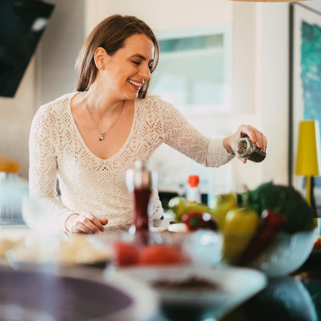 Beautiful young casually dressed woman preparing healthy food and seasoning salad in the kitchen at home