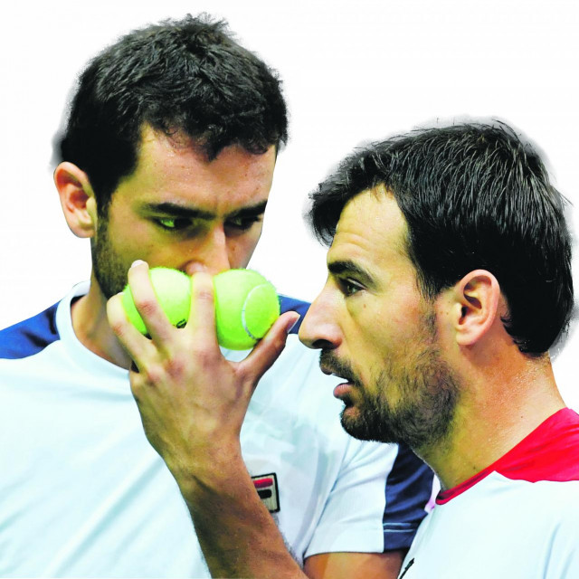 """Croatia's Marin Cilic (L) and Ivan Dodig (R) discuss tactics before serving the ball to France's Pierre-Hugues Herbert and Nicolas Mahut during the Davis Cup World Group semifinal doubles match between Croatia and France at """"Kresimir Cosic"""" hall in Zadar, on September 17, 2016. (Photo by ANDREJ ISAKOVIC/AFP)"""