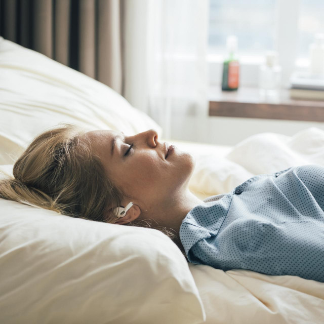 Happy blonde woman in blue pajamas lying in bed in the morning and listening to relaxing music.