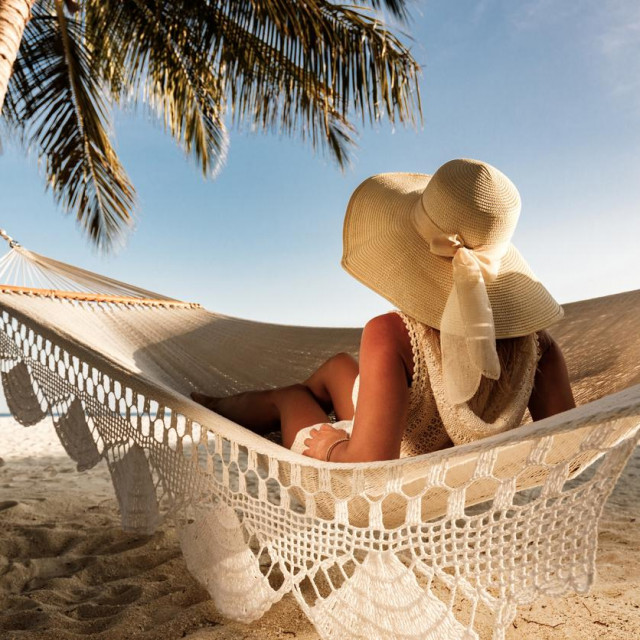 Rear view of a woman with sun hat relaxing in hammock during summer day on the beach and looking at view.
