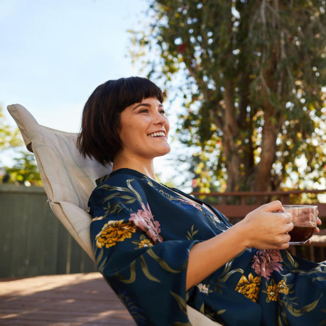 Smiling young woman wearing a robe and lying on a deck chair outside drinking a cup of tea