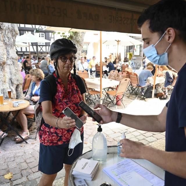 Konobar provjerava covid potvrdu u restoran