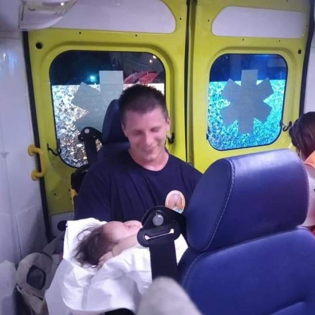 Riječki vatrogasac drži bebu u kolima Hitne pomoći
