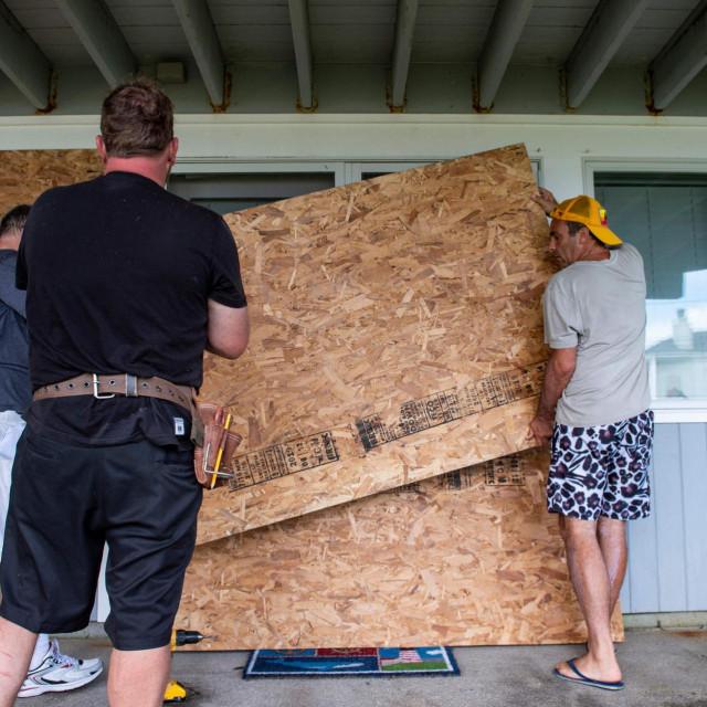 Građevinski radnici osiguravaju kuće na obali uoči dolaska uragana Henri