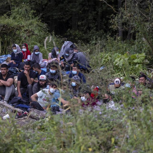 Migranti za koje se vjeruje da su iz Afganistana sjede na tlu u malom selu Usnarz Gorny u blizini Bialystoka, sjeveroistočna Poljska