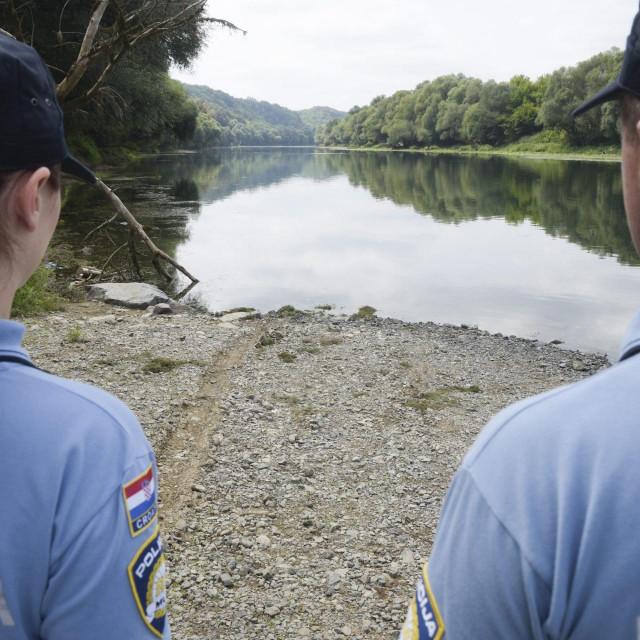 Policajci stoje uz rijeku/Ilustracija